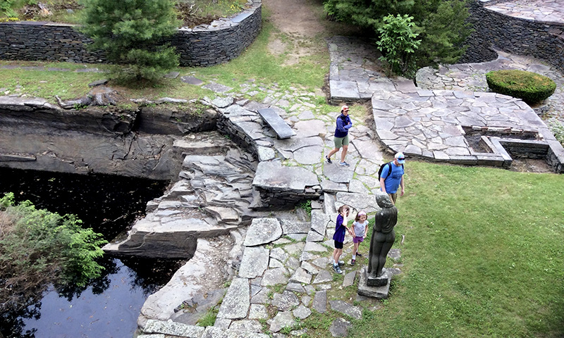 aerial photo of Opus 40 fountain with statue and tourists