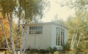 Small white cabin in the woods, used as a studio