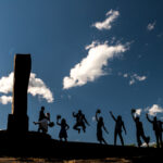 Bridal party jumping Opus 40 monolith, in front of blue sky and white clouds.
